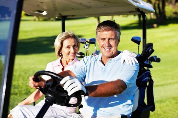 Portrait of happy mature couple sitting in golf car and ready for a game